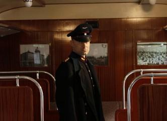 Theo Plakoudakis als Paul Ogorzow; uniformiert in der S-Bahn stehend.